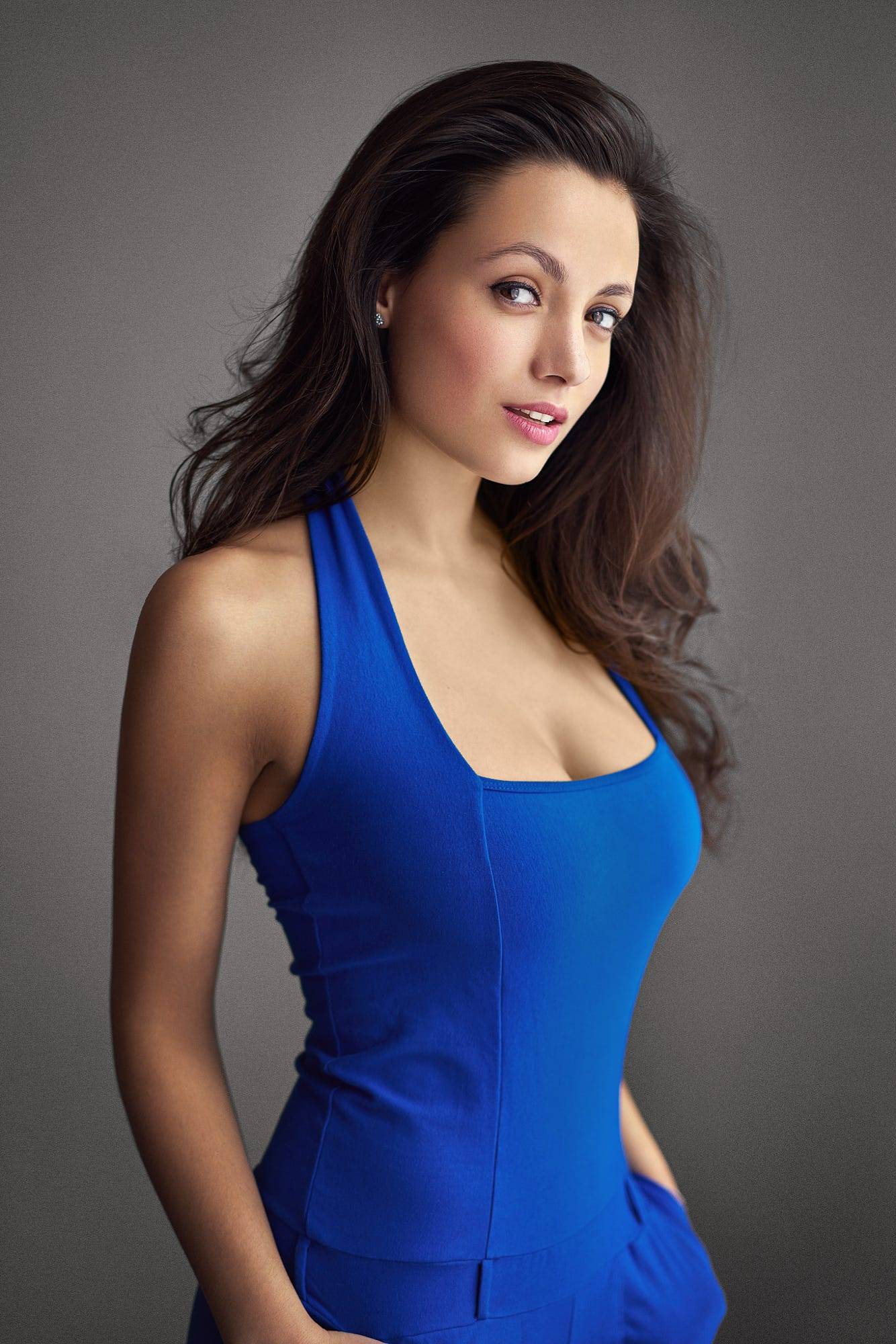 People 1334x2000 women brunette long hair wavy hair looking at viewer dress blue clothing cleavage blue dress simple background smiling make up eyeliner blush lipstick jewelry earring hands in pockets blue clothes Tereza Dušková czech Czech women