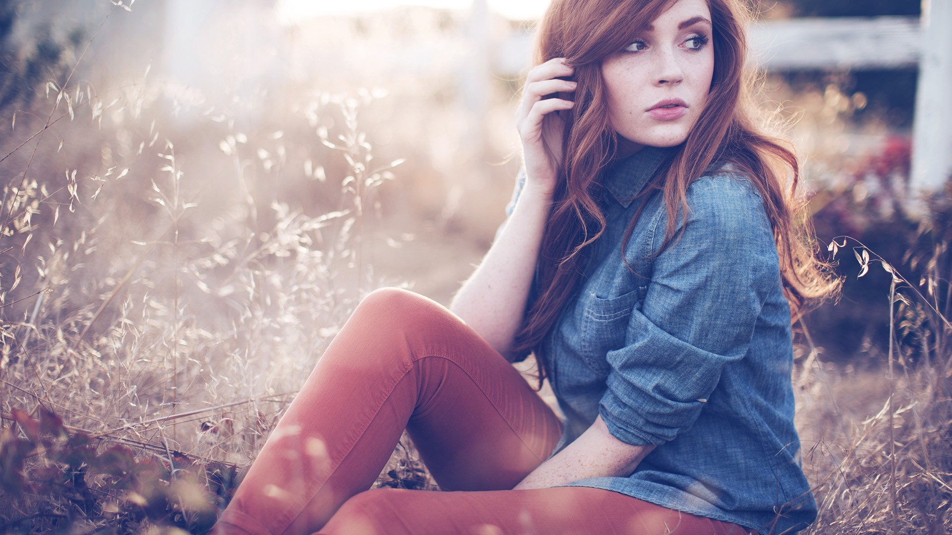 People 1920x1080 redhead women freckles women outdoors photography bokeh model grass depth of field jeans field looking away hands in hair sitting long hair outdoors touching hair