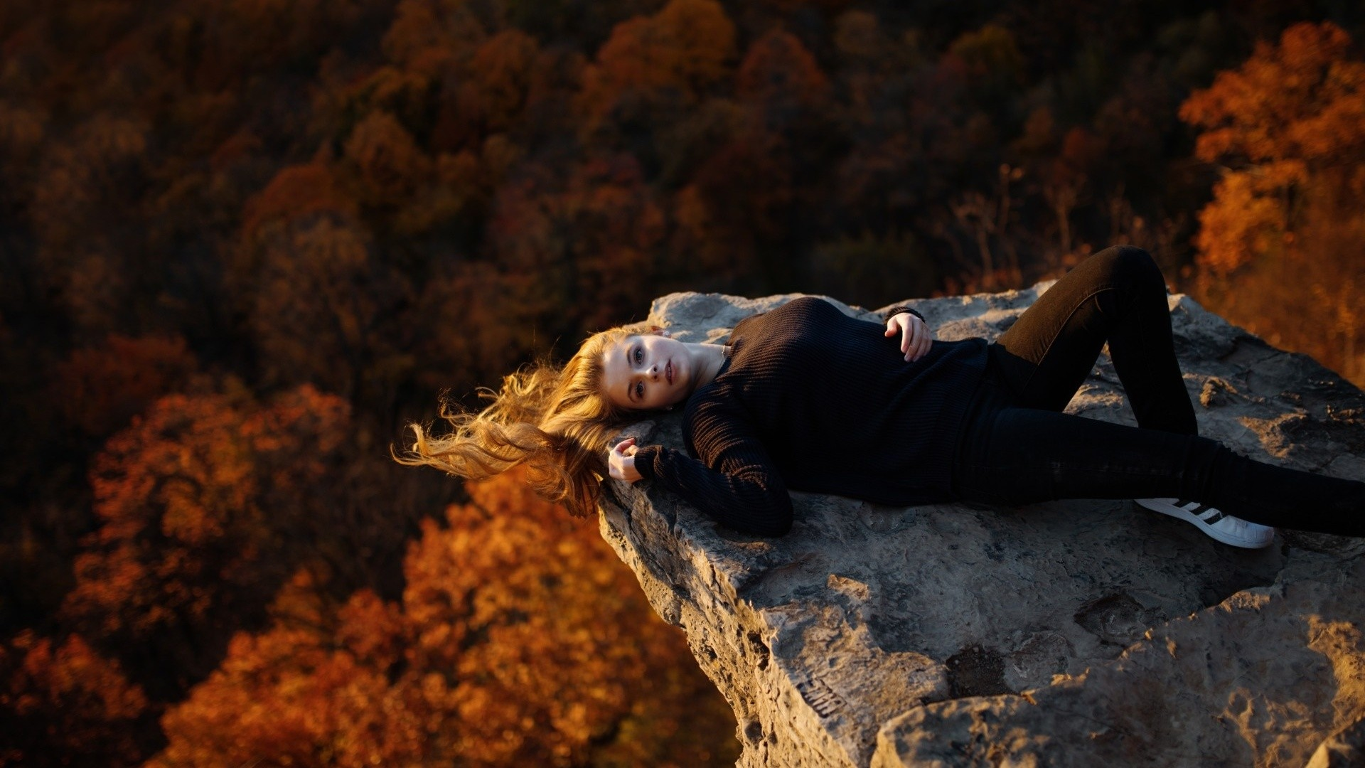 People 1920x1080 women model blonde long hair women outdoors nature trees lying on back looking at viewer black clothing open mouth rock forest windy sneakers Adidas skinny jeans fall blue eyes black sweater black pants hair hanging down