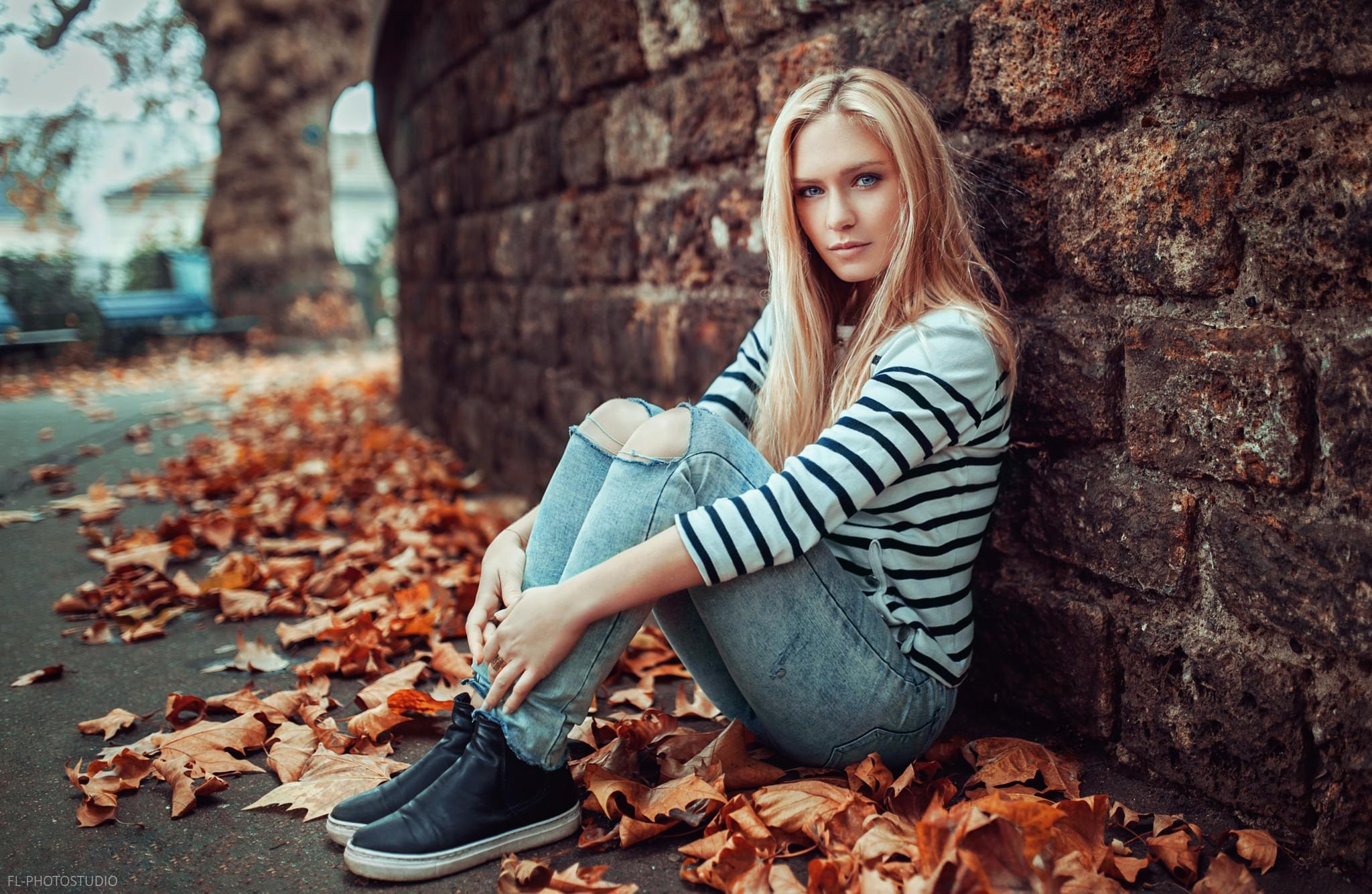 People 2048x1334 women blonde sitting looking at viewer pants jeans torn jeans sneakers leaves wall urban fall Eva Mikulski Lods Franck depth of field portrait sweatshirts