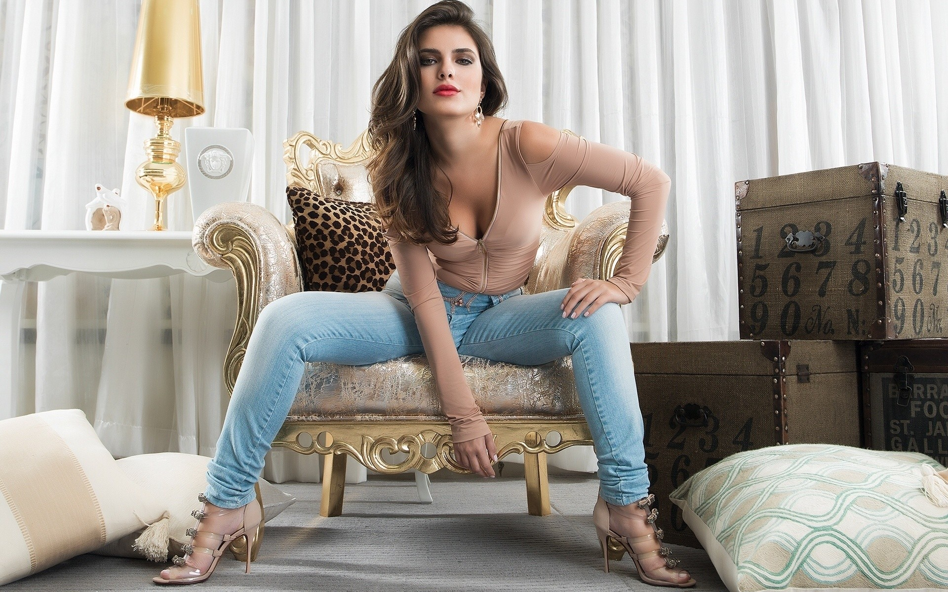 People 1920x1200 high heels jeans brunette animal print boxes chair pillow women lamp cleavage red lipstick long hair model