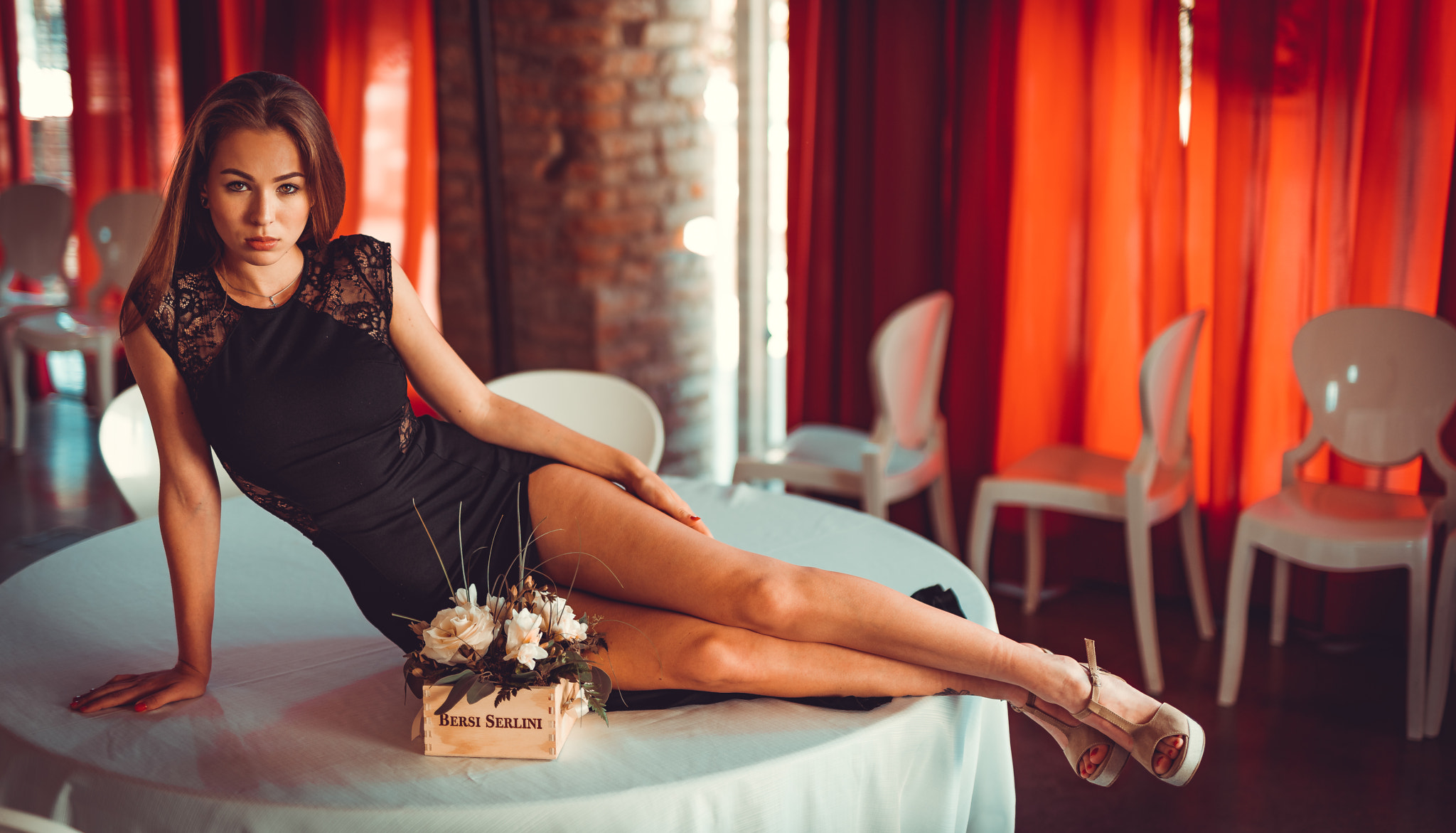 People 2048x1171 women Marco Squassina black dress high heels table red nails portrait women indoors high cut dress brunette lying on side long hair