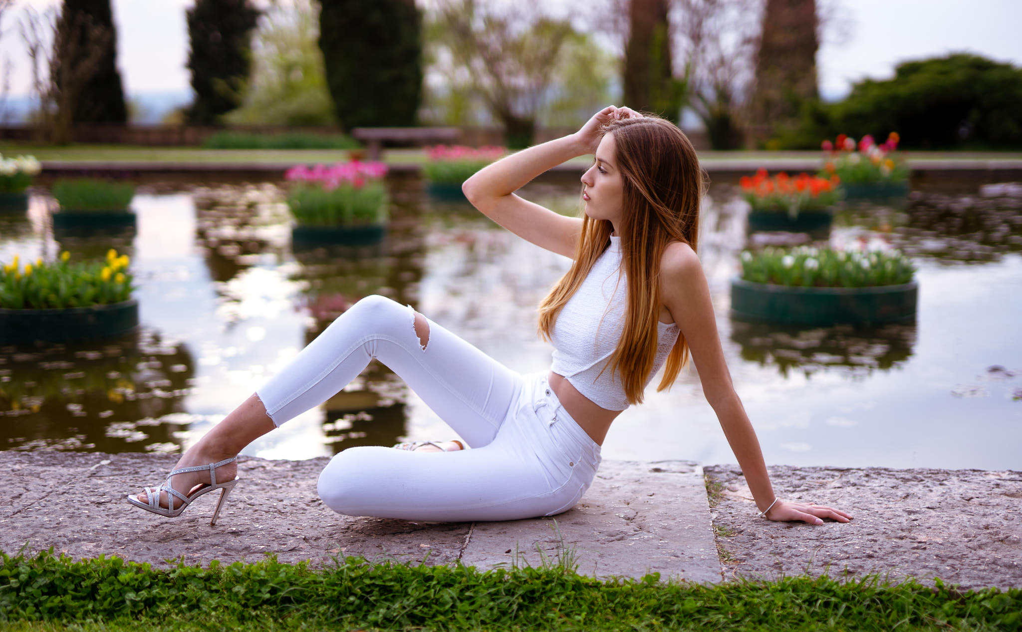 People 2048x1266 women Marco Squassina high heels jeans white clothing sitting long hair women outdoors flowers looking away torn jeans grass