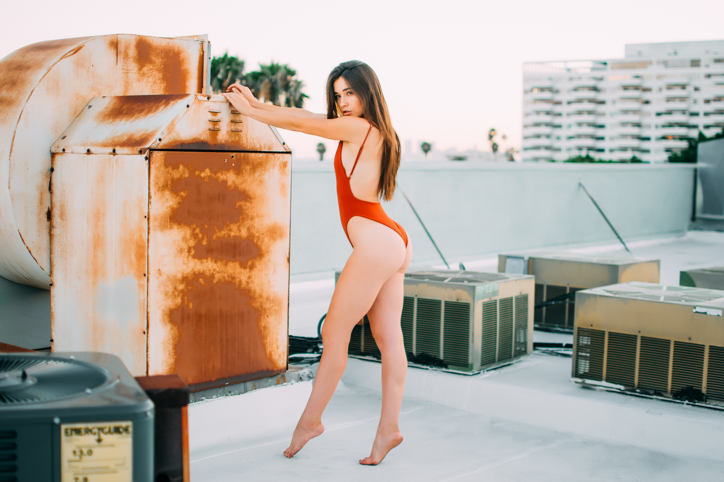 People 2500x1667 Audrey Bradford model Christian Montoya one-piece swimsuit monokinis ass women brunette long hair looking at viewer sensual gaze barefoot standing rooftops depth of field women outdoors tiptoe