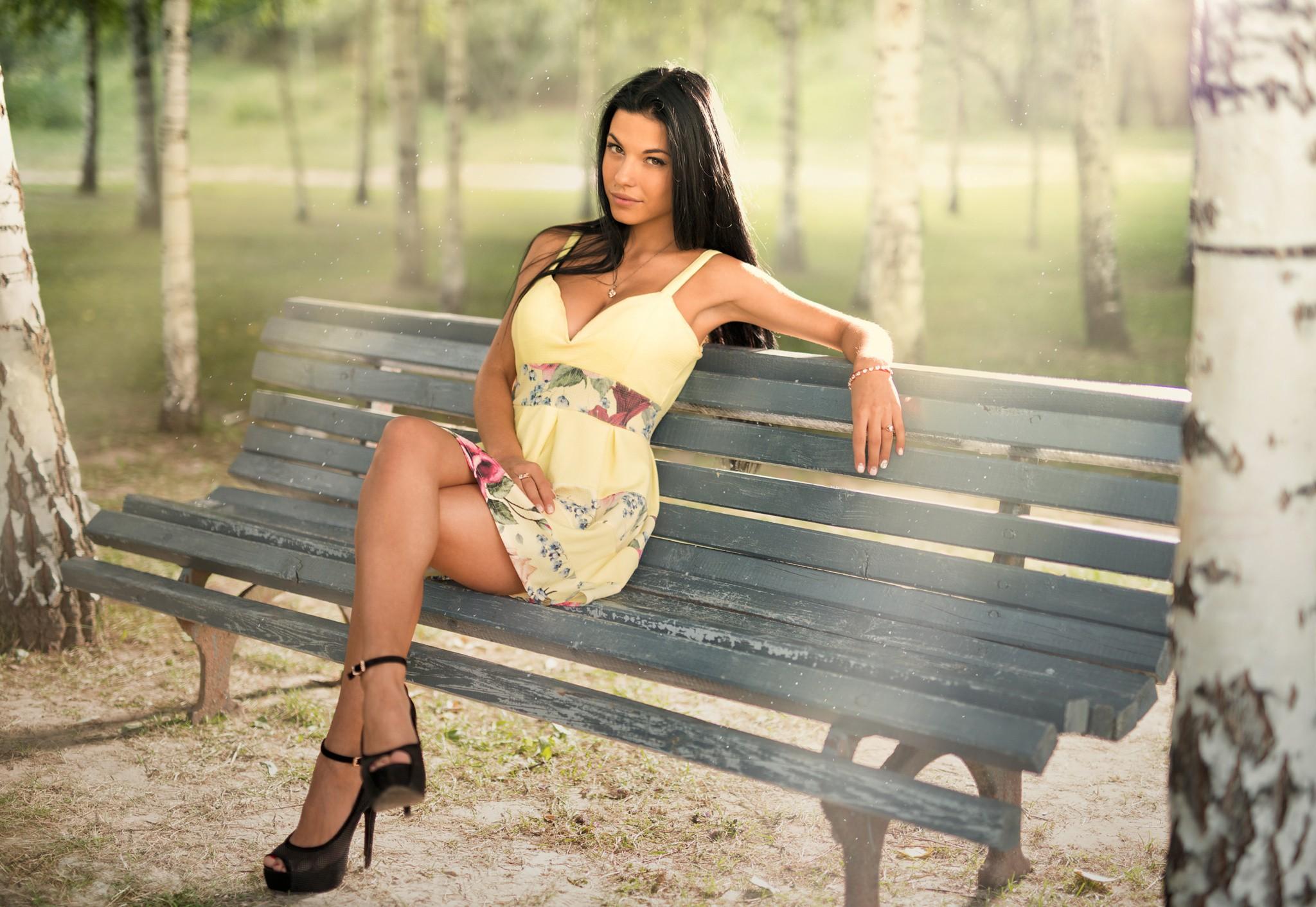 People 2048x1412 Marina Shimkovich women sitting dress high heels bench yellow dress outdoors trees looking at viewer heels black heels summer dress legs crossed model
