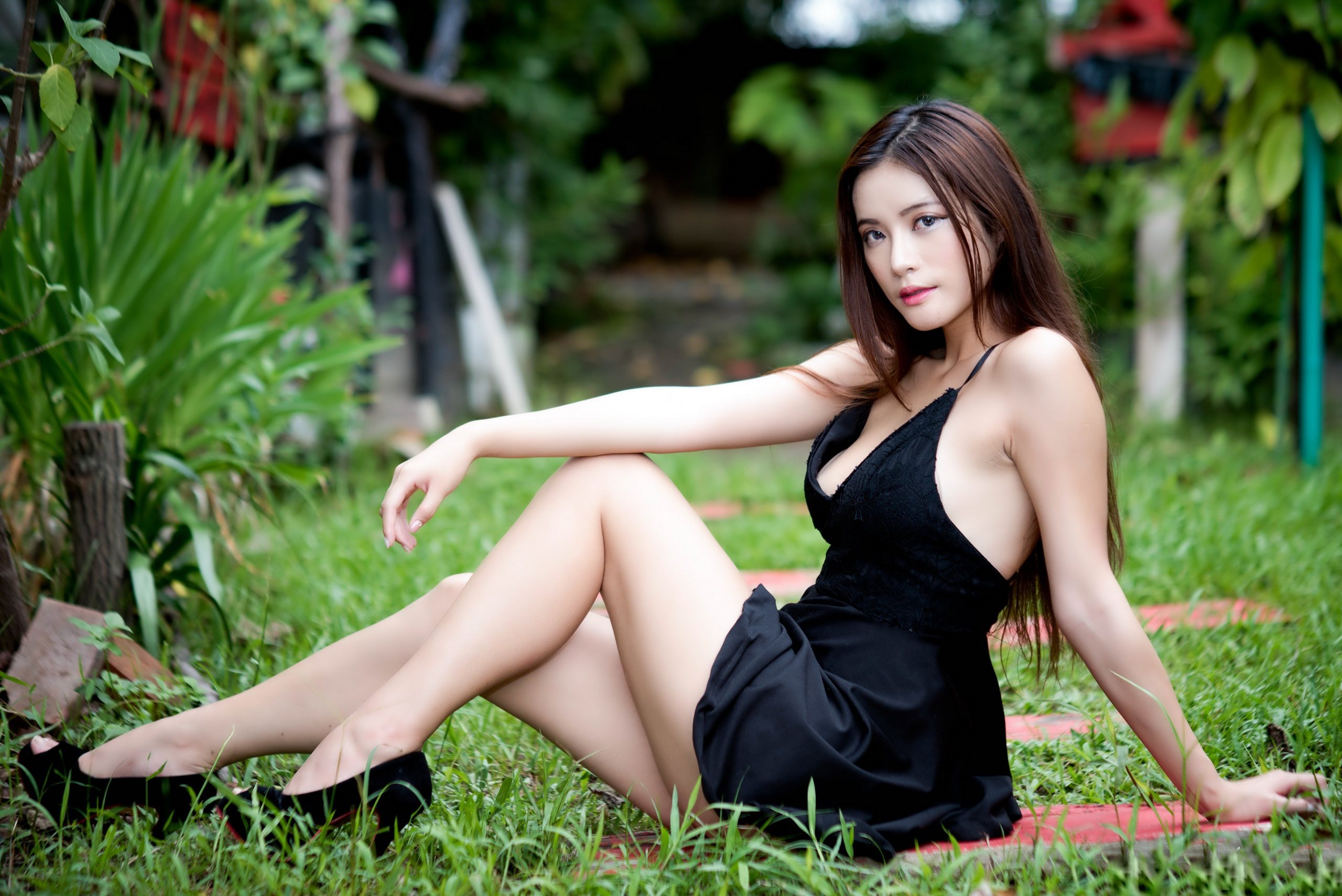 People 2560x1709 Asian women black dress high heels sitting grass women outdoors long hair legs cleavage eyeliner looking at viewer fake iris