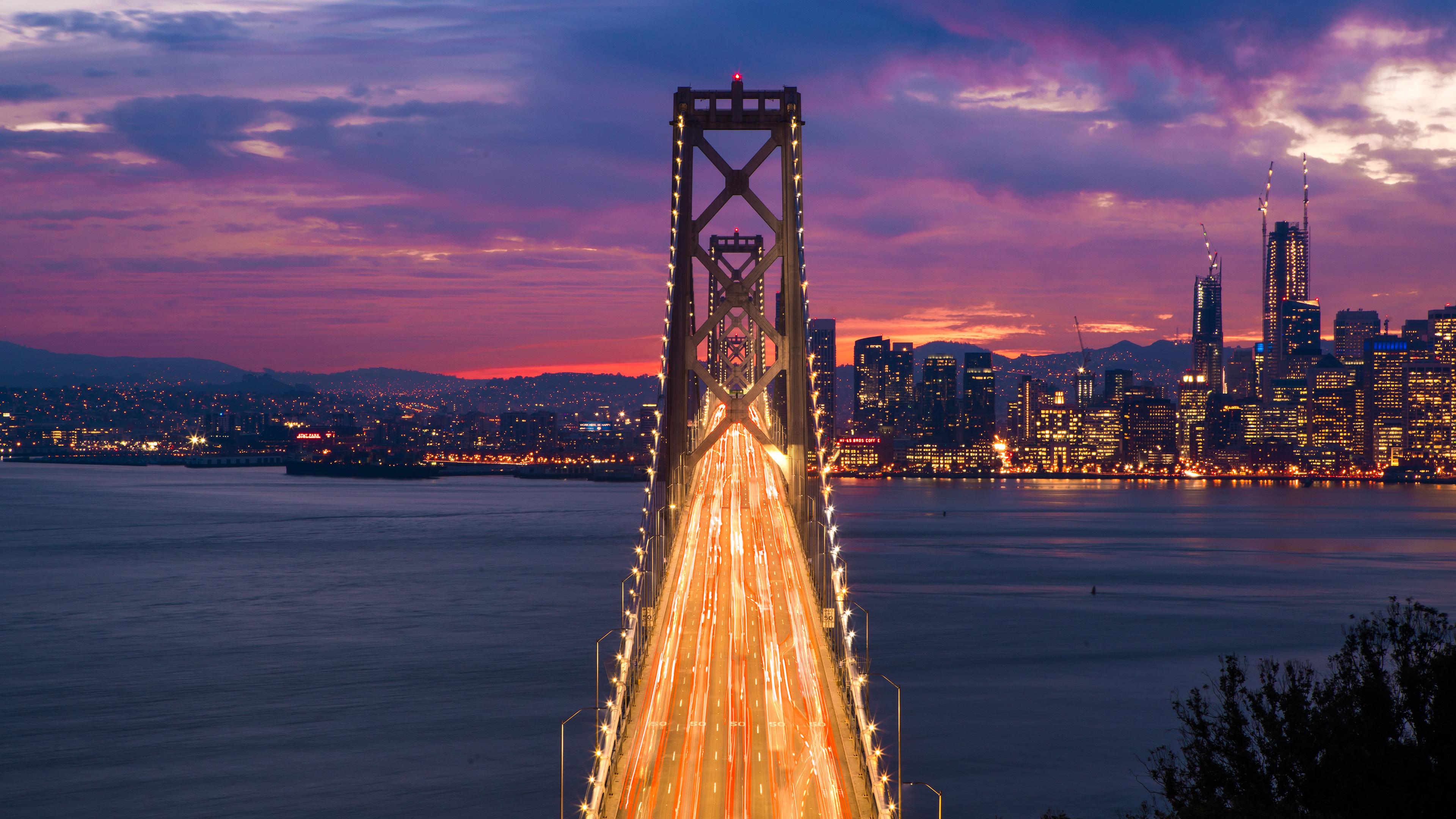 General 3840x2160 architecture cityscape skyscraper evening sunset water bridge clouds city lights motion blur San Francisco USA light trails San Francisco-Oakland Bay Bridge city purple sky